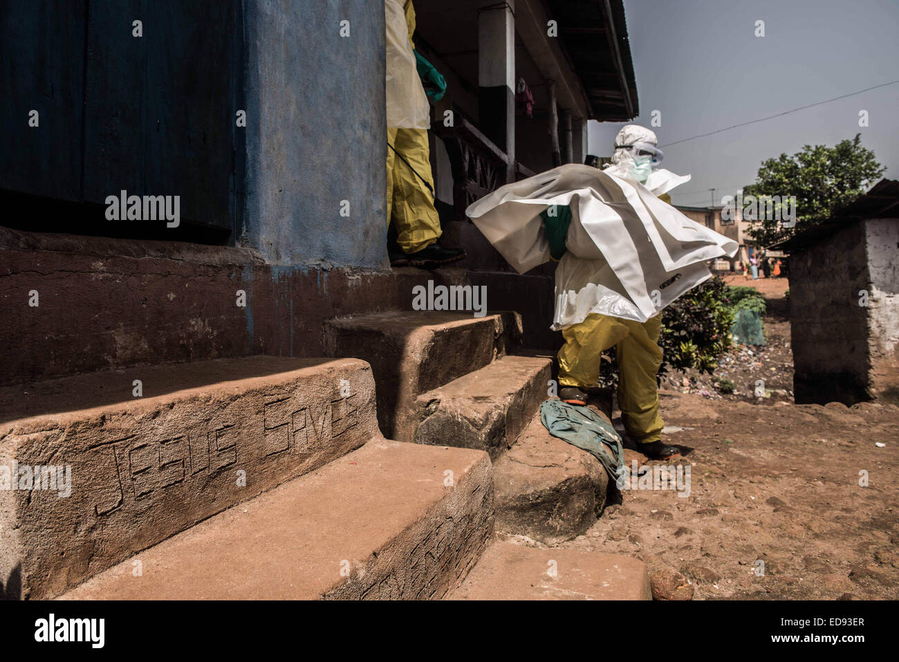A burial team member removes the body of a baby from a house in Freetown. Unsafe burials are one of the leading - Stock Image