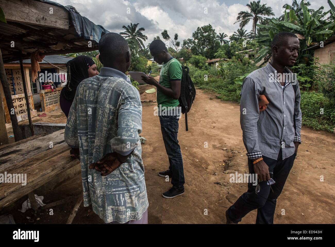 Surveillance officers talk with the family of an Ebola patient in Waterloo. Tracing and isolating people who have - Stock Image