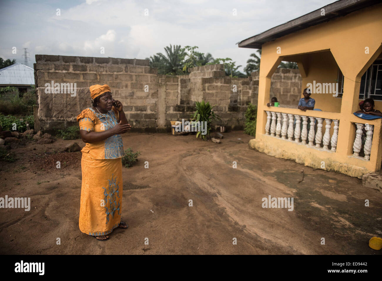 Saffiatu Blango calls for an ambulance to collect a man suspected of having Ebola. Saffiatu is responsible for tracing - Stock Image