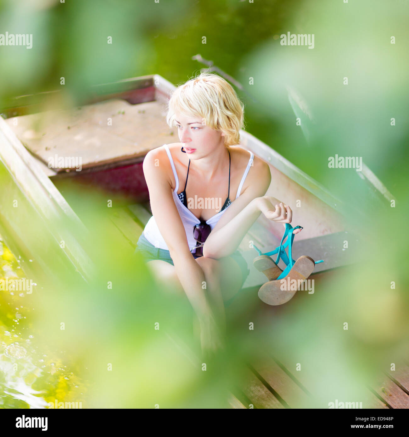 Woman relaxing on the vintage wooden boat. Stock Photo