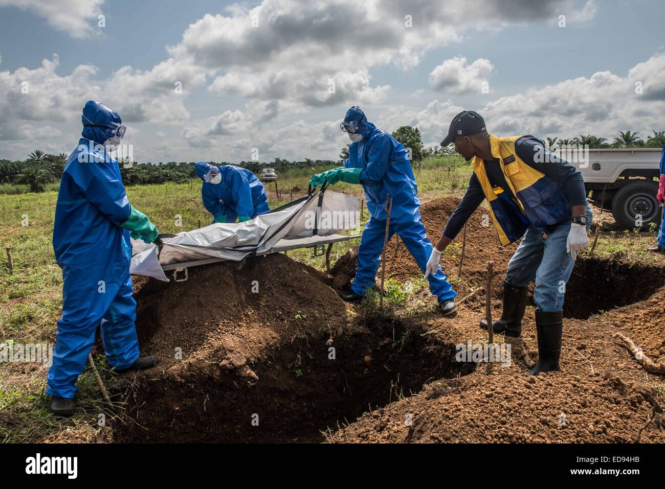 A burial team buries the body of a young woman who died in an Ebola holding center in Makeni. With Ebola spreading - Stock Image