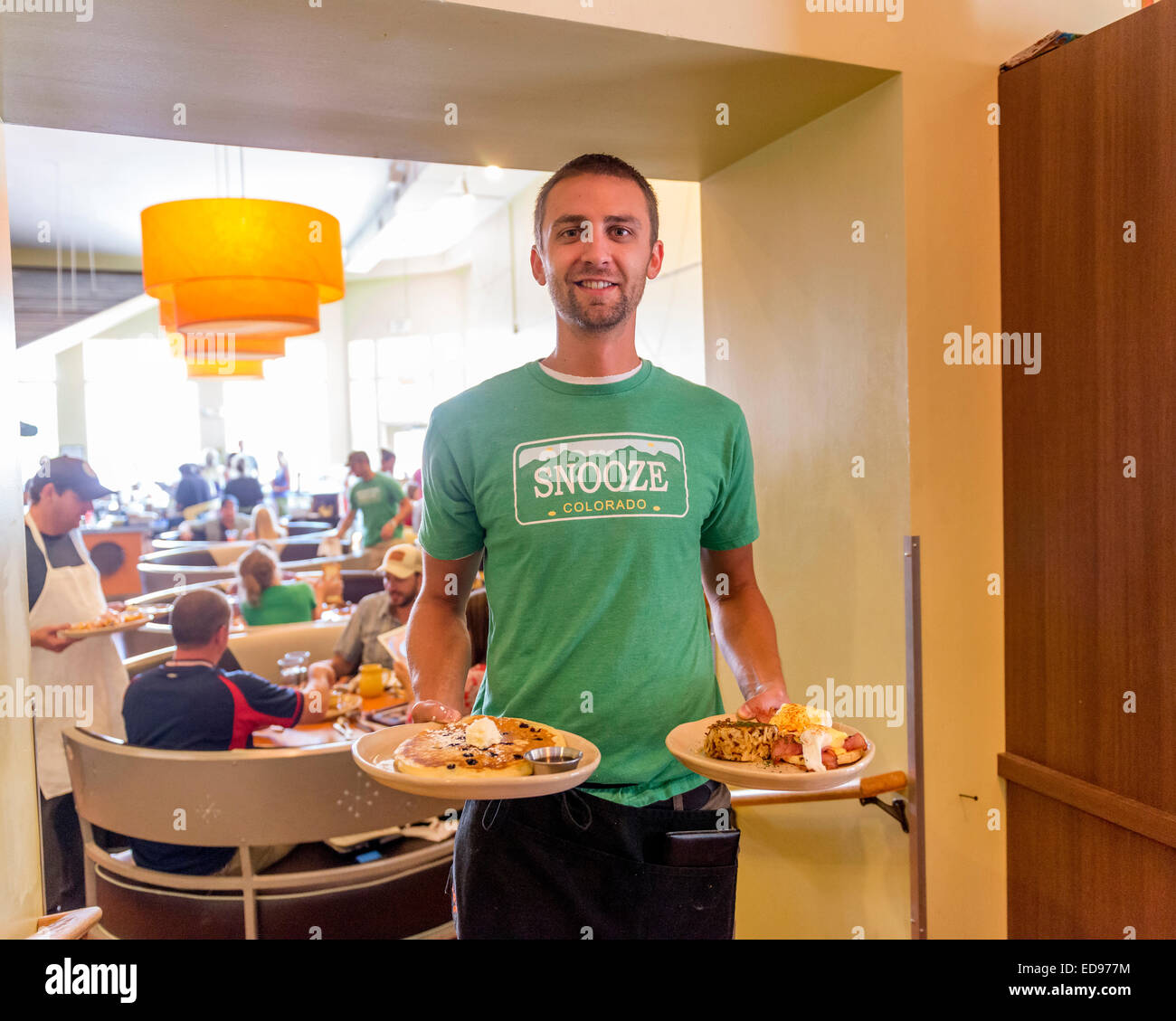 Waiter holding American breakfasts at Snooze an AM Eatery. Denver. Colorado. USA - Stock Image