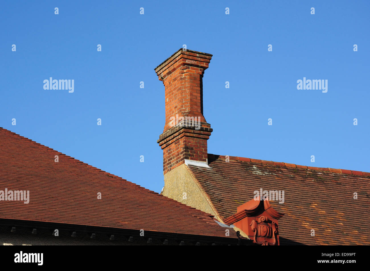 Tiled roofs and chimney stack on old buildings, Hitchin, Hertfordshire, England, UK - Stock Image
