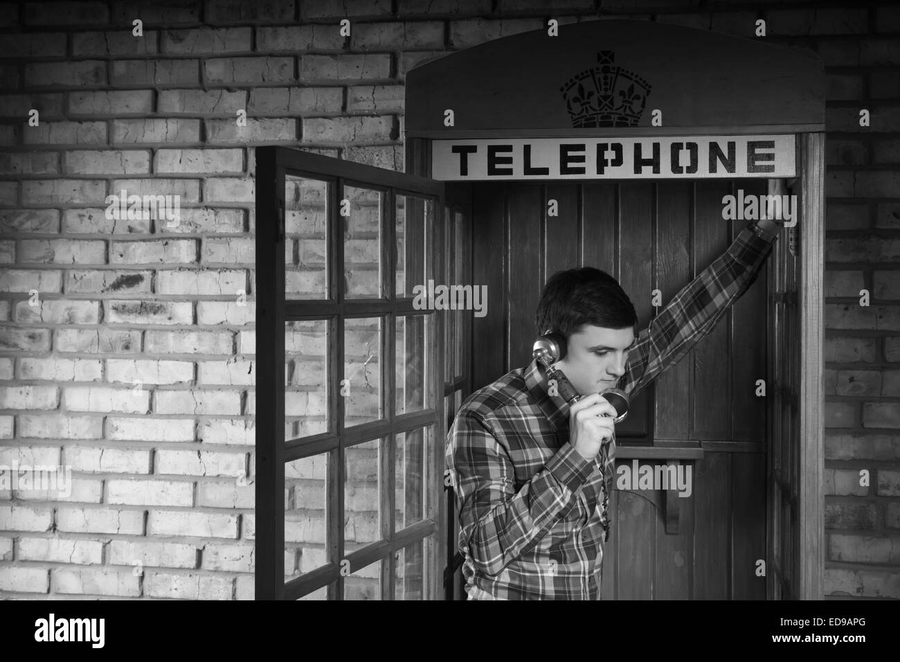 Young Man Calling Someone at the Telephone Booth with Brick Wall Background. Captured in Monochrome. - Stock Image