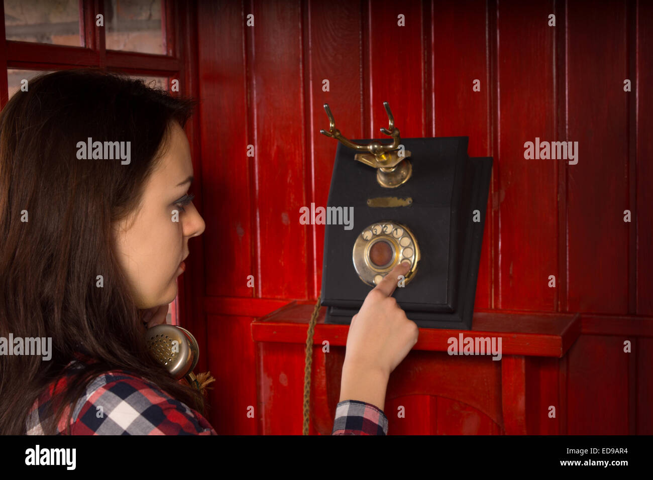 Woman dialing out on a vintage telephone instrument in a wooden red phone booth - Stock Image