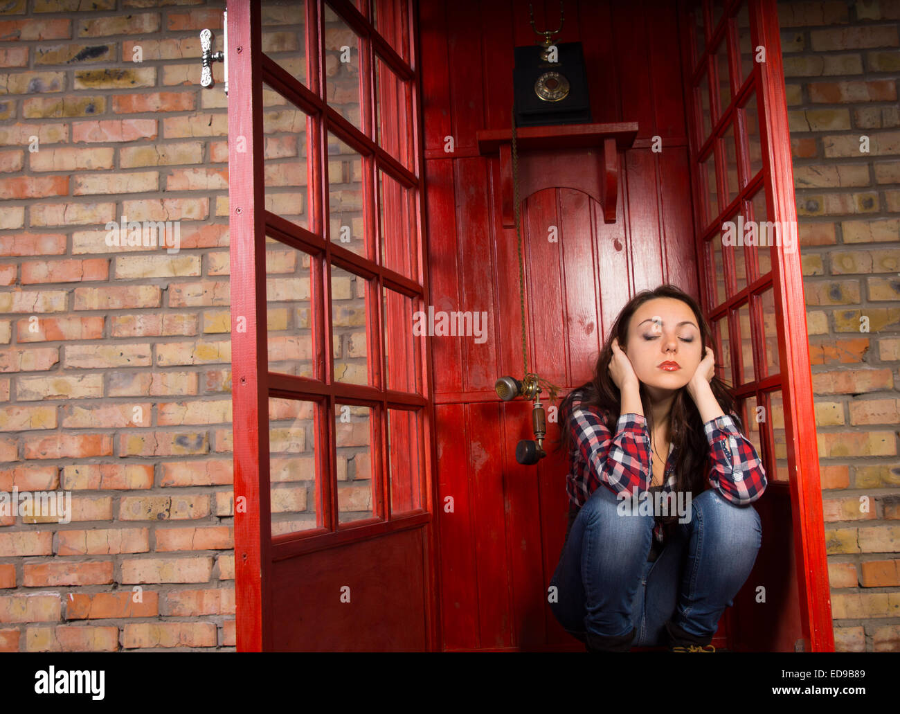 Upset woman sitting blocking her ears in a telephone booth as the handset dangles alongside her ear - Stock Image