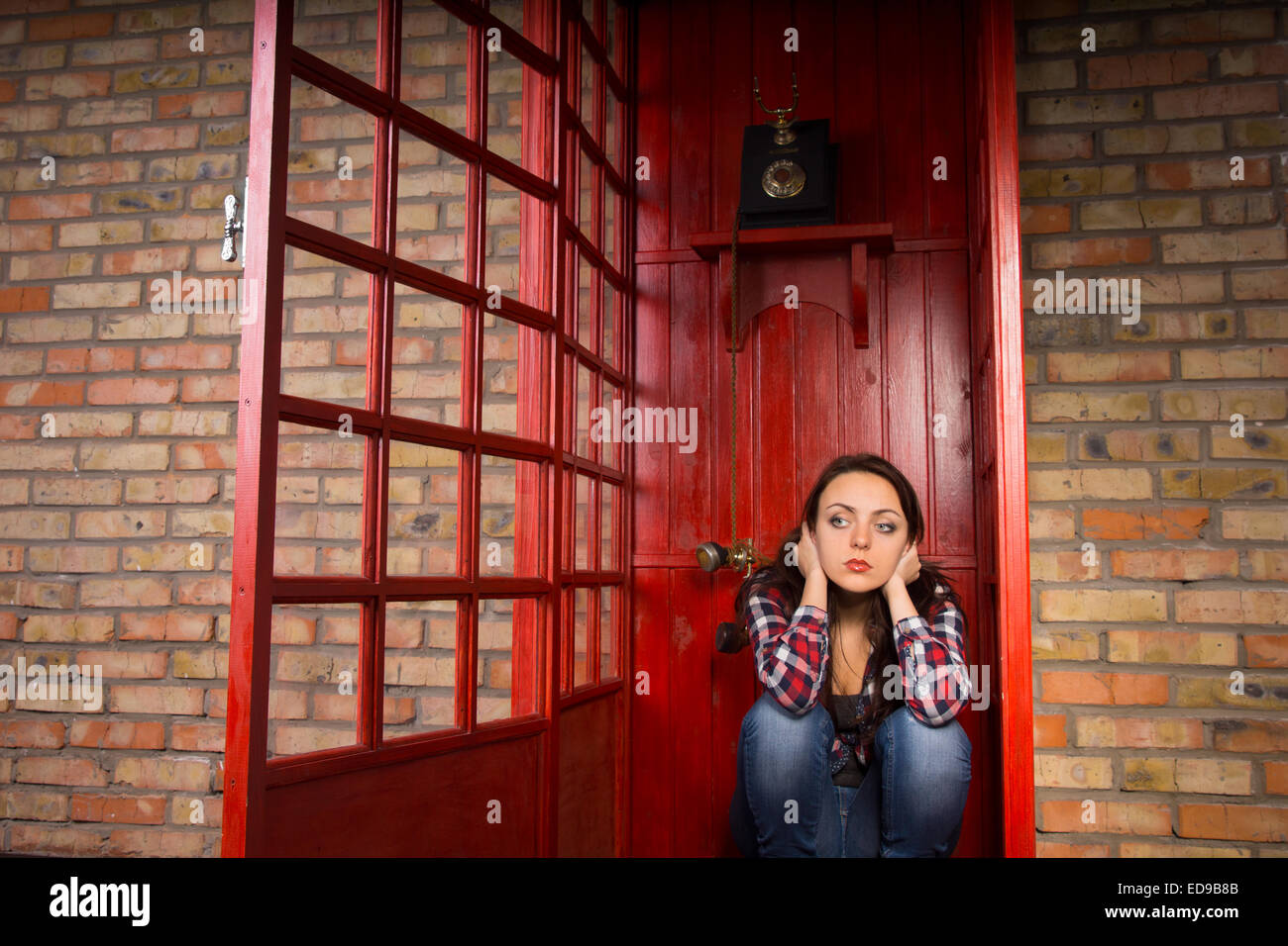 Troubled Young Woman with Hands Over Ears Crouching in Red Telephone Booth with Open Door - Stock Image