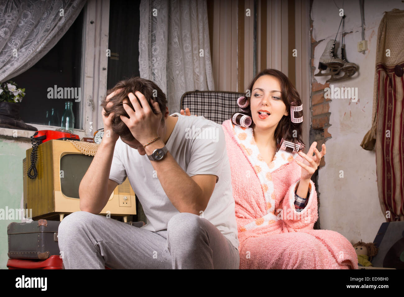 Couple in a run down retro room sitting arguing with the wife in her dressing gown gesturing and talking while the - Stock Image