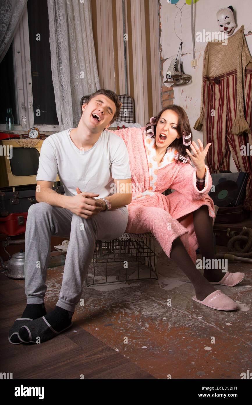 Handsome young man yelling in frustration at his wife at her constant nagging as they sit together in a squalid - Stock Image