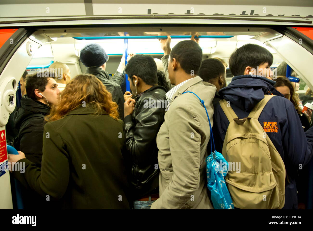 Crowds of commuters board a London Underground train at Oxford Circus railway station on the Victoria Line, London, - Stock Image