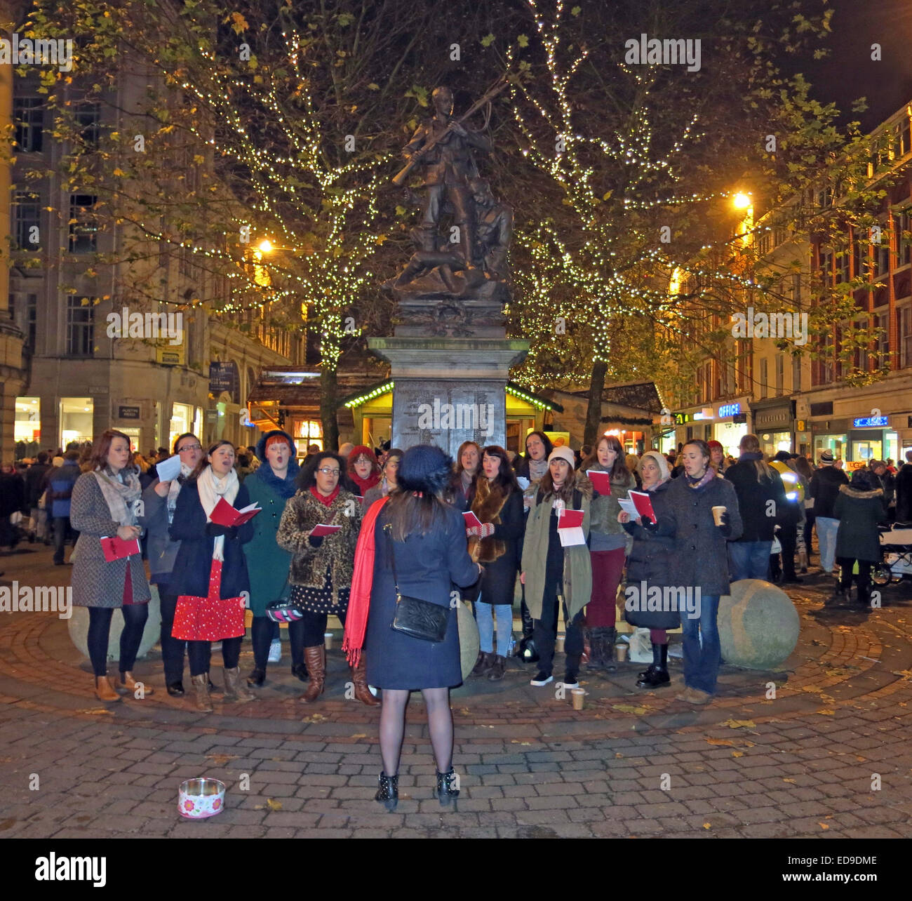 Traditional Carol Singers Manchester St Annes Sq, England, UK at night - Stock Image