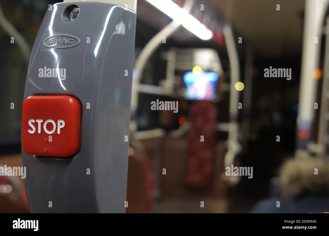 Red Stop button on a public bus, Lothian Scotland, out of focus (with Braille ) at night Stock Photo
