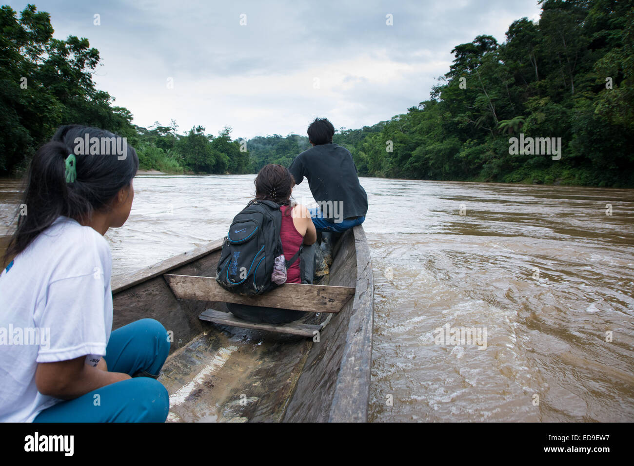 People traveling by dugout canoe along Rio Cenepa in the Amazon jungle region of Northern Peru - Stock Image