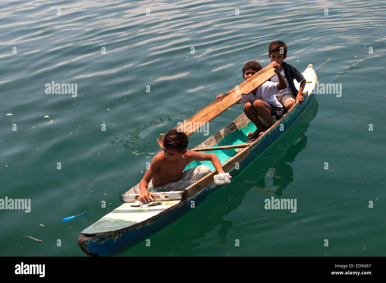 Indonesian children in a canoe in the waters of Wuring fishing village near Maumere on Flores island, Indonesia. - Stock Image