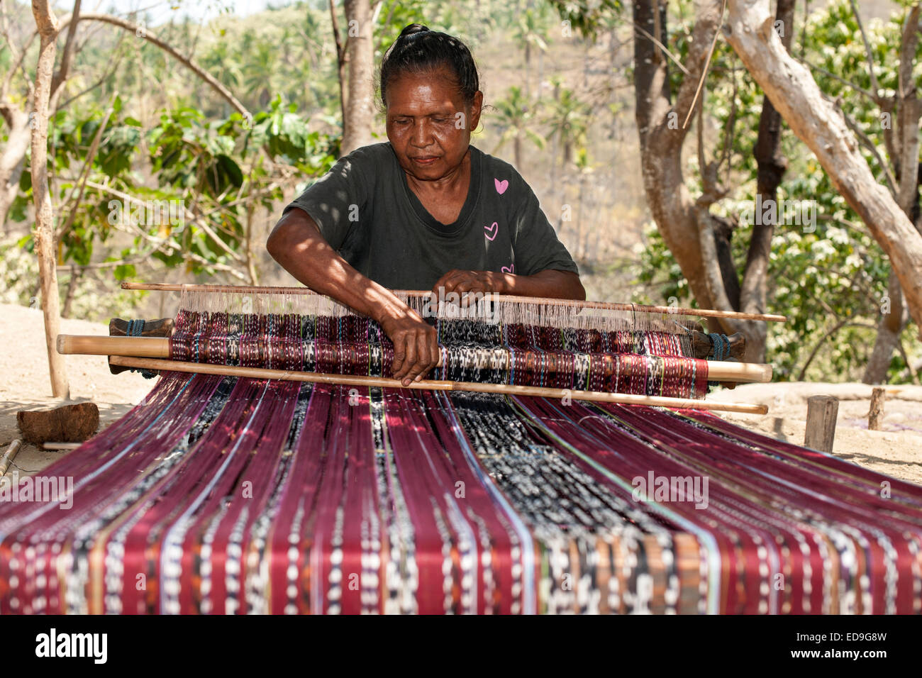 Indonesian woman weaving traditional sarongs on the roadside on the island of Flores in Indonesia. - Stock Image