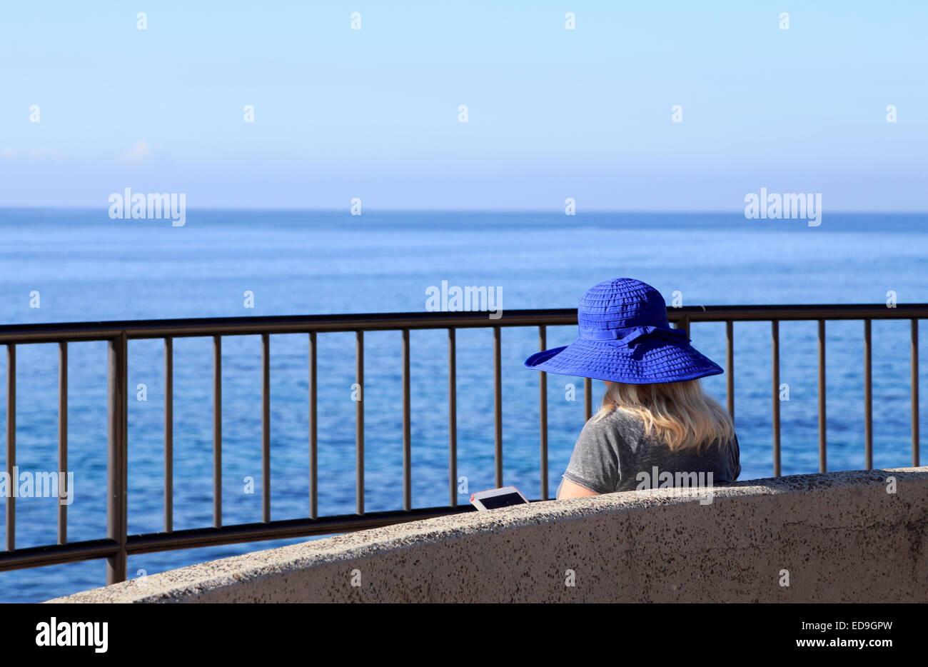 Woman reading ebook with view over the ocean - Stock Image
