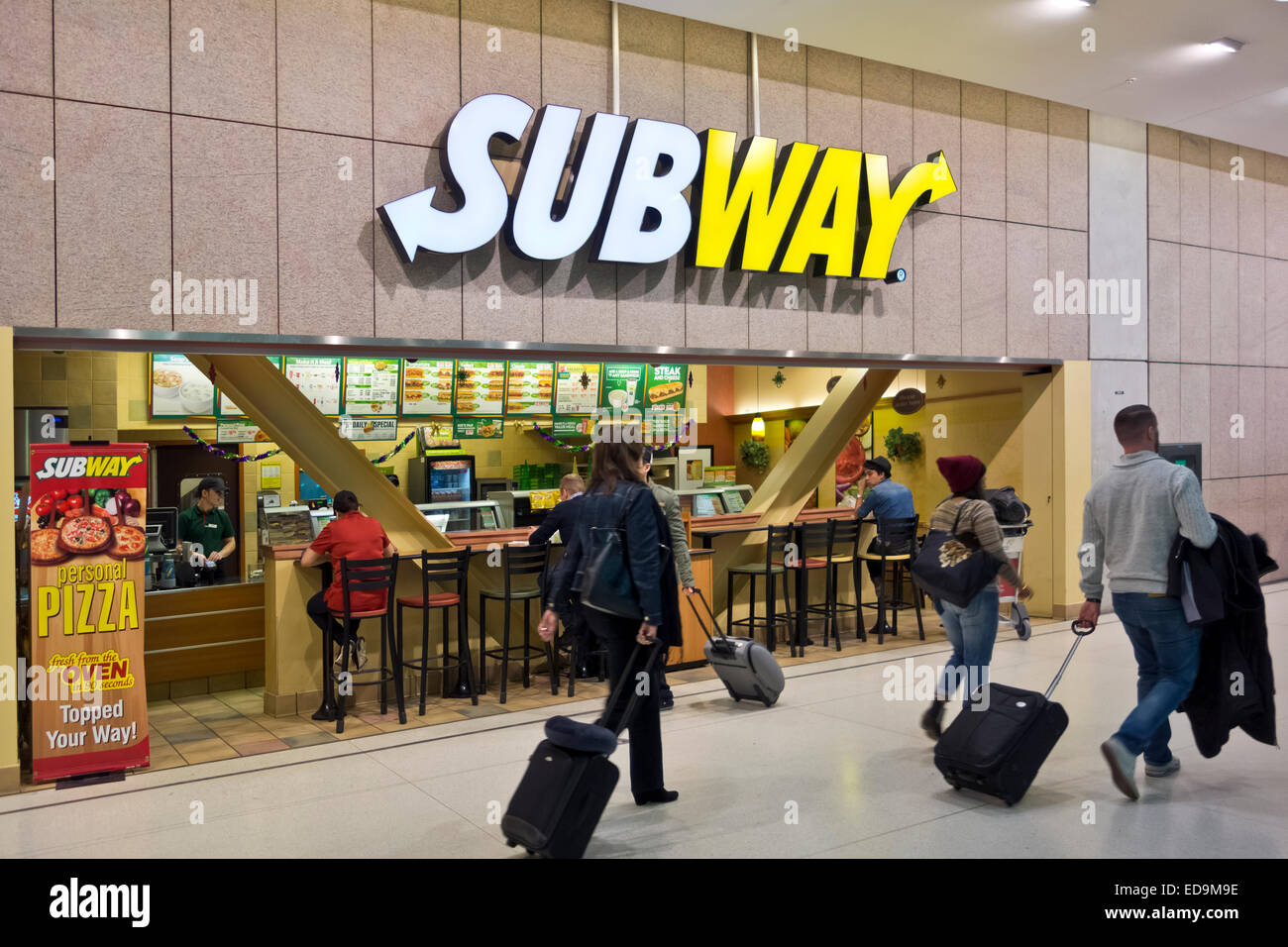 Air travelers with suitcases pass by a Subway sandwich restaurant at Toronto Airport, Canada.  Fast food meals. Stock Photo