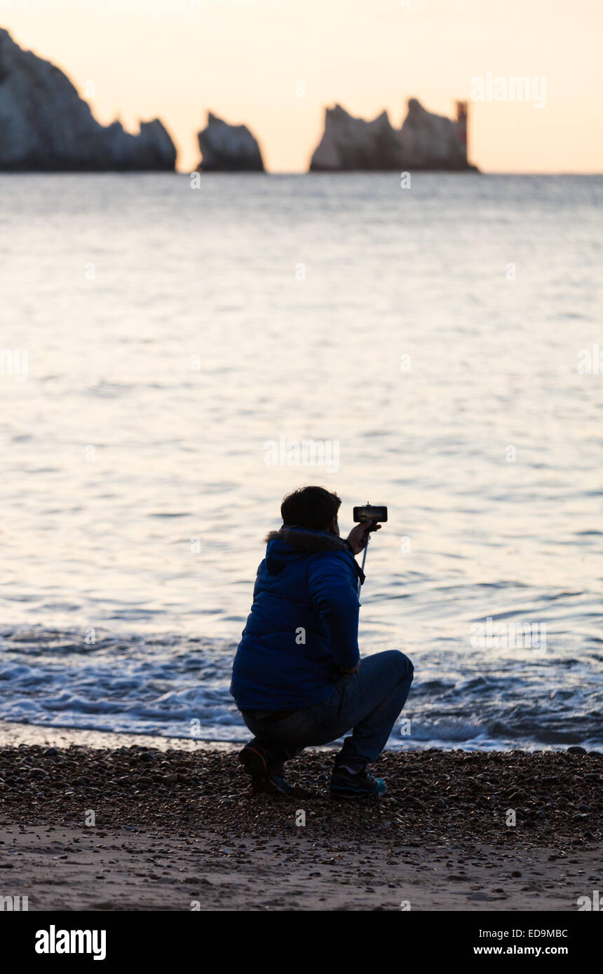 A man with a 'selfie stick' at Alum Bay on the Isle of Wight with the Needles in the distance - Stock Image