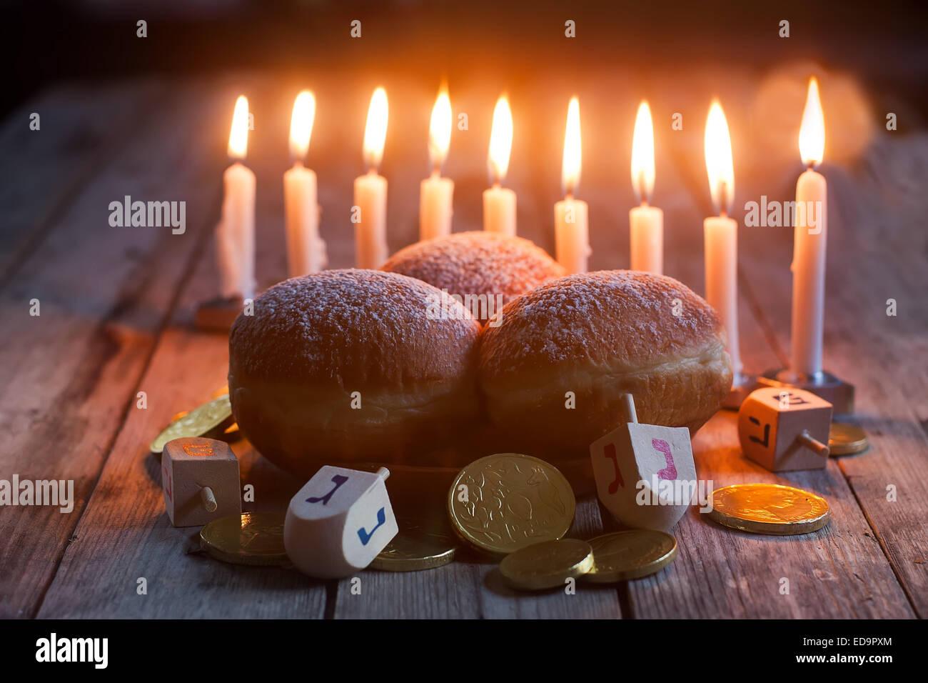 Jewish holiday hannukah symbols - menorah, doughnuts, chocolate coins and wooden dreidels. - Stock Image