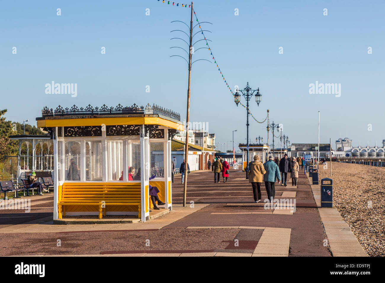 People walking along Southsea seafront promenade near Portsmouth with yellow shelter and a blue sky on a fine winter Stock Photo