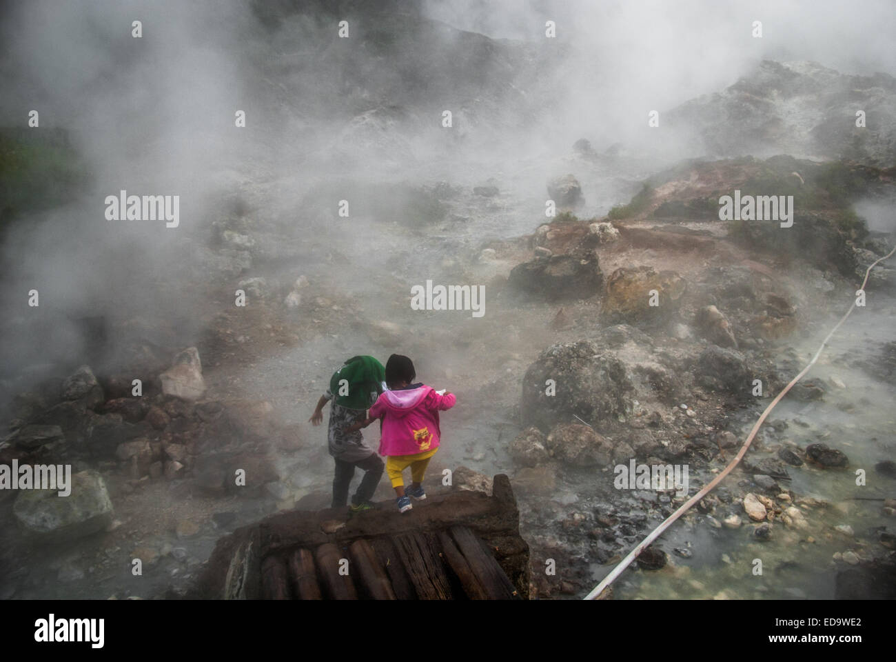 Children passing through a hazy fumarole field in North Sulawesi, Indonesia. - Stock Image