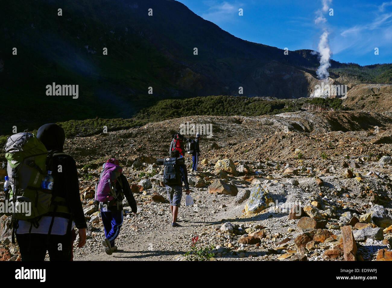 Local climbers pass through Mount Papandayan's crater. - Stock Image