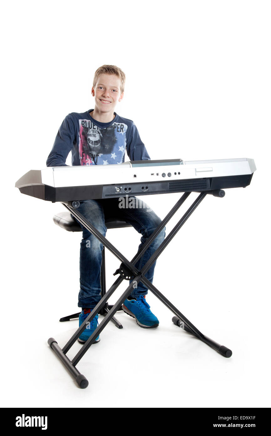 teenage boy sitting at keyboard playing music - Stock Image