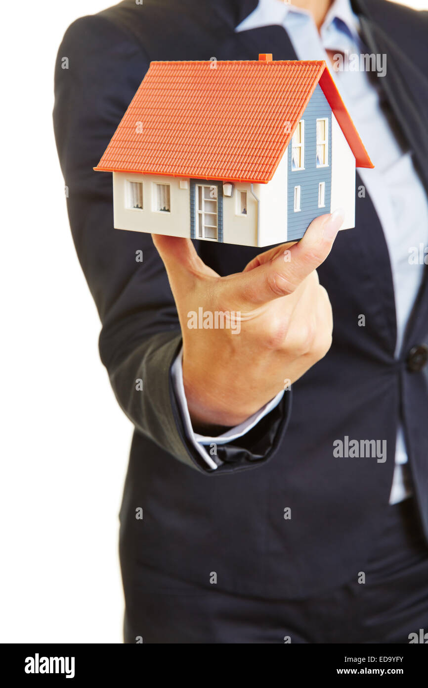 Hands of a female real estate broker holding a small house as concept for a home Stock Photo
