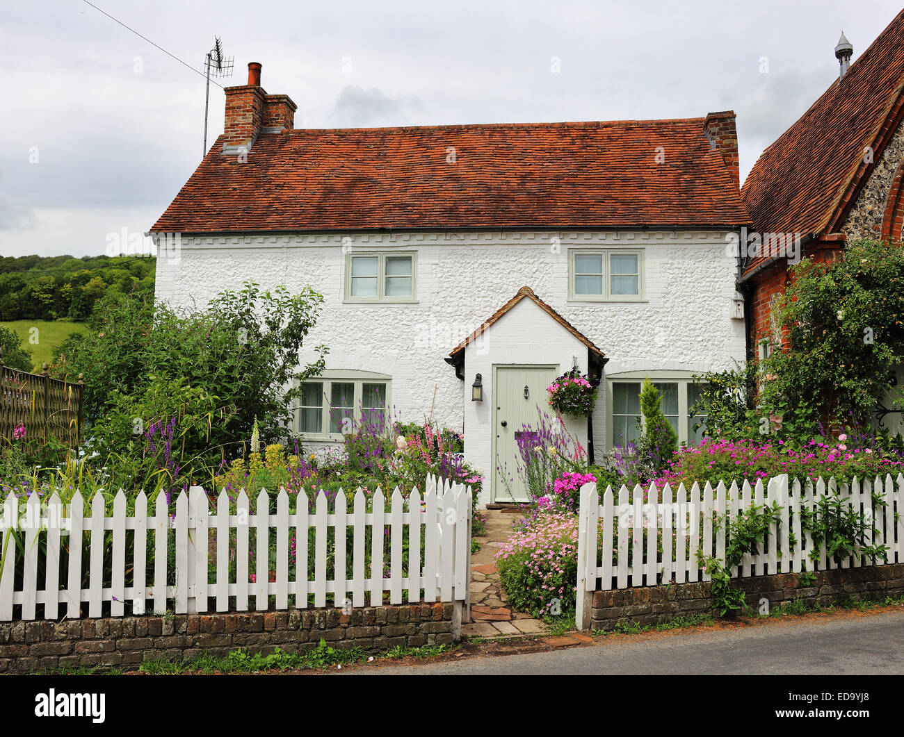 Traditional whitewashed English rural Stone Cottage and garden with picket fence - Stock Image