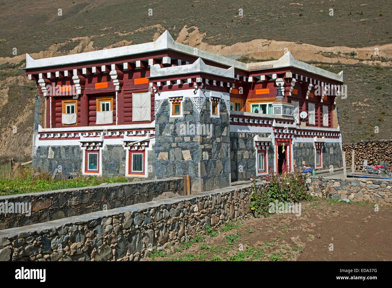 Tibetan architecture on countryside showing modern granite house with typical flat roof and little watchtower, Sichuan, - Stock Image
