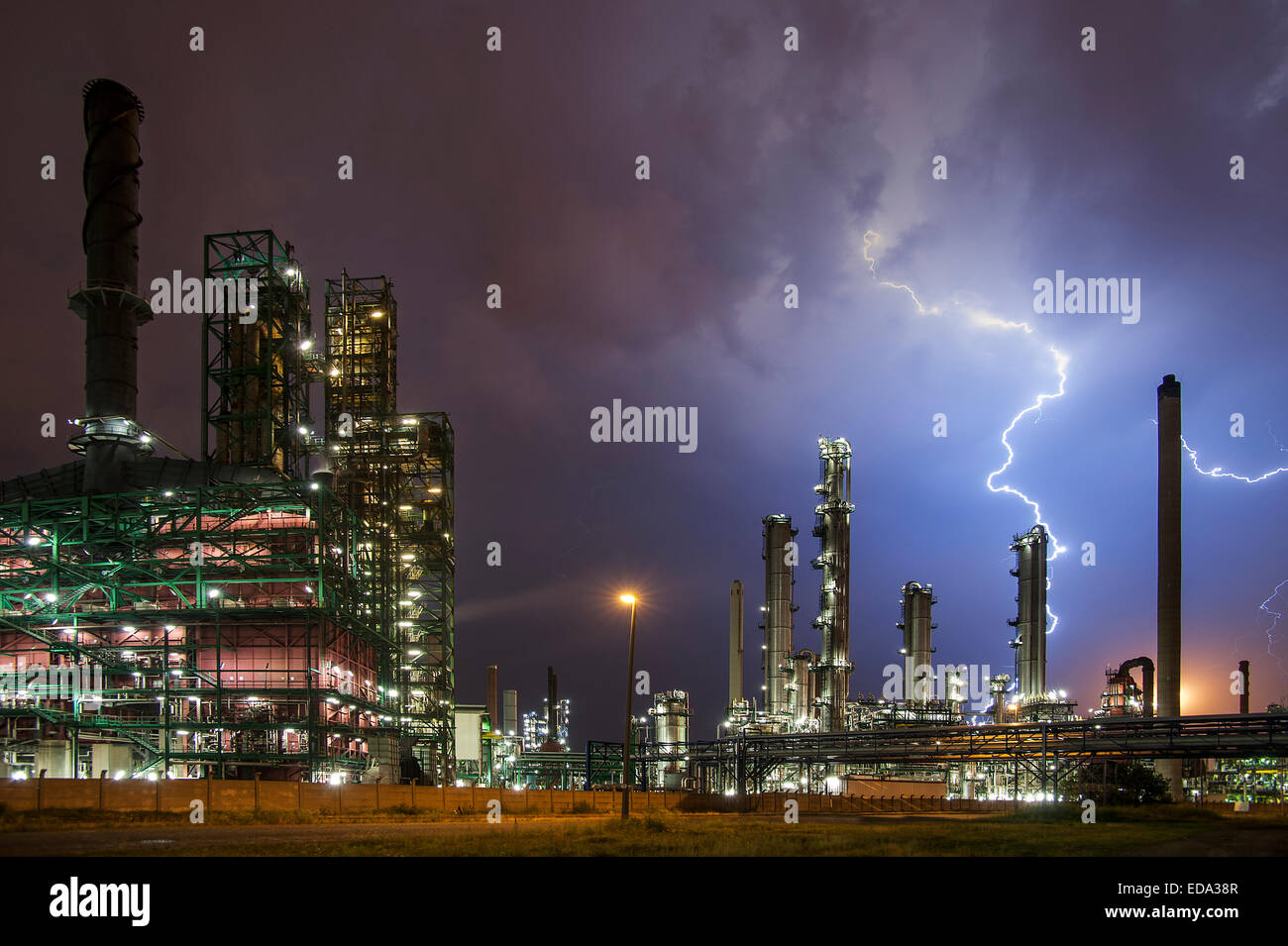 Lightning bolts striking oil refinery at industrial estate during heavy thunderstorm conceptual picture for global - Stock Image