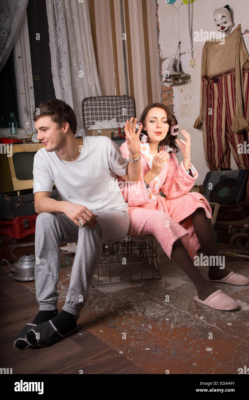Young Man in Casual Clothing Refusing to Listen his Partner in Bath Robe While Sitting on Cage at Junk Room - Stock Image