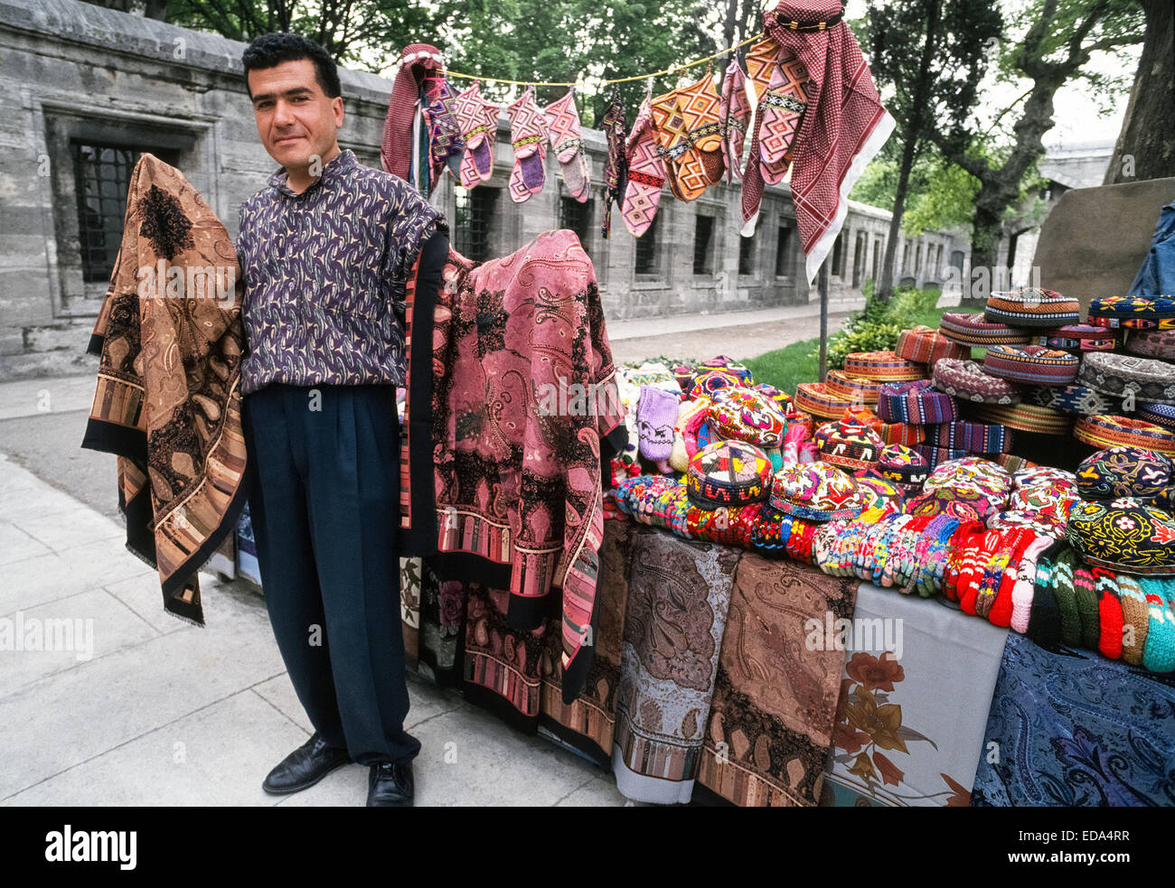 A male vendor displays patterned shawls and very colorful knit caps and woven hats at his outdoor stand in Istanbul, - Stock Image