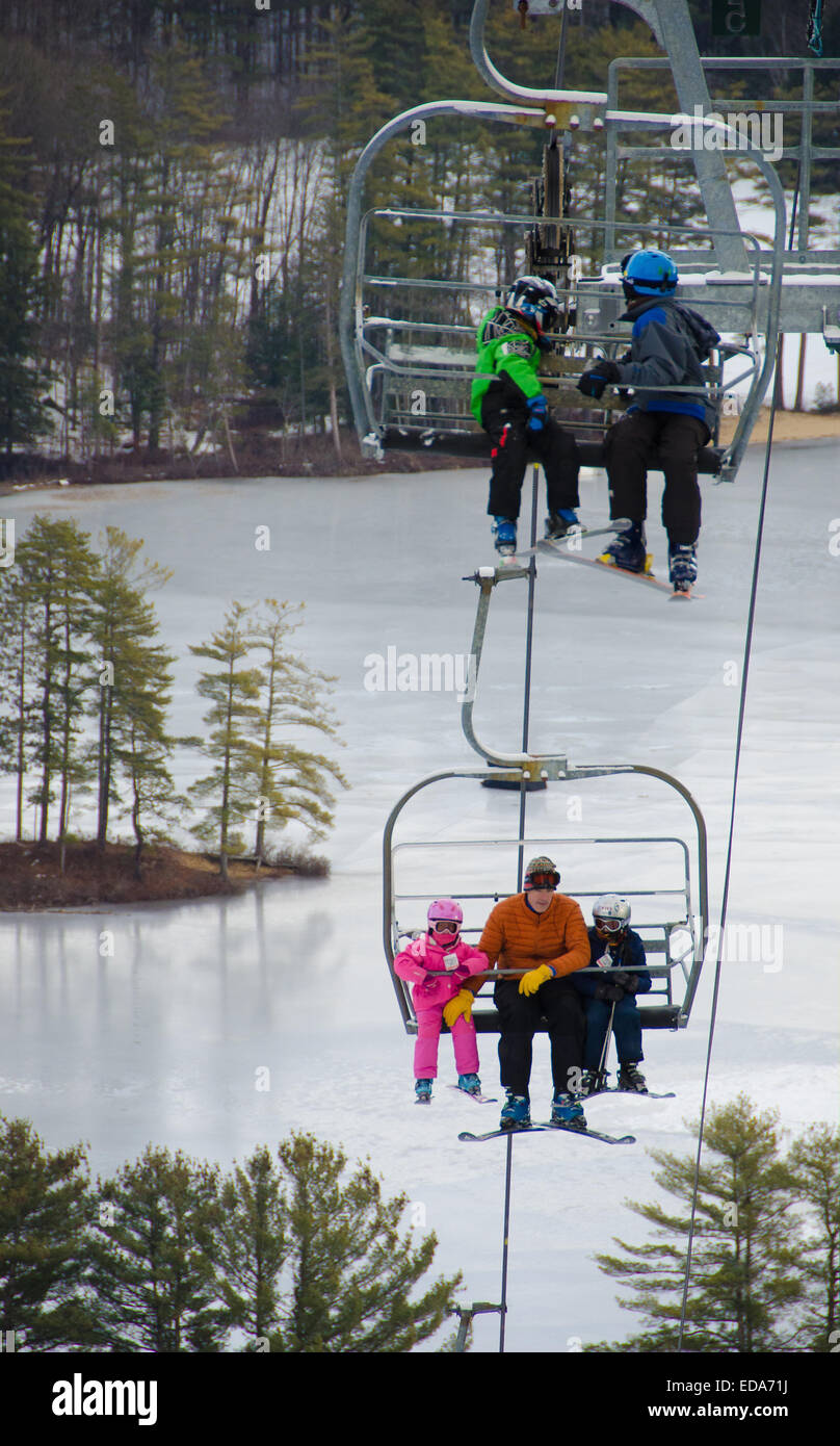 Skiers and snowboarders ascend to the top of Madison, New Hampshire's King Pine ski slope via a chairlift. - Stock Image