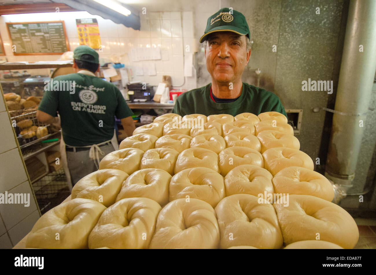Kettle-boiled bagels are transported to the oven for its final stage of preparation at New York City's Ess-a - Stock Image