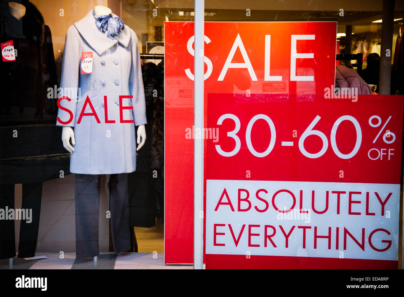 020d5422a4 Large sale sign posters in a shop window showing clothes on sale ...