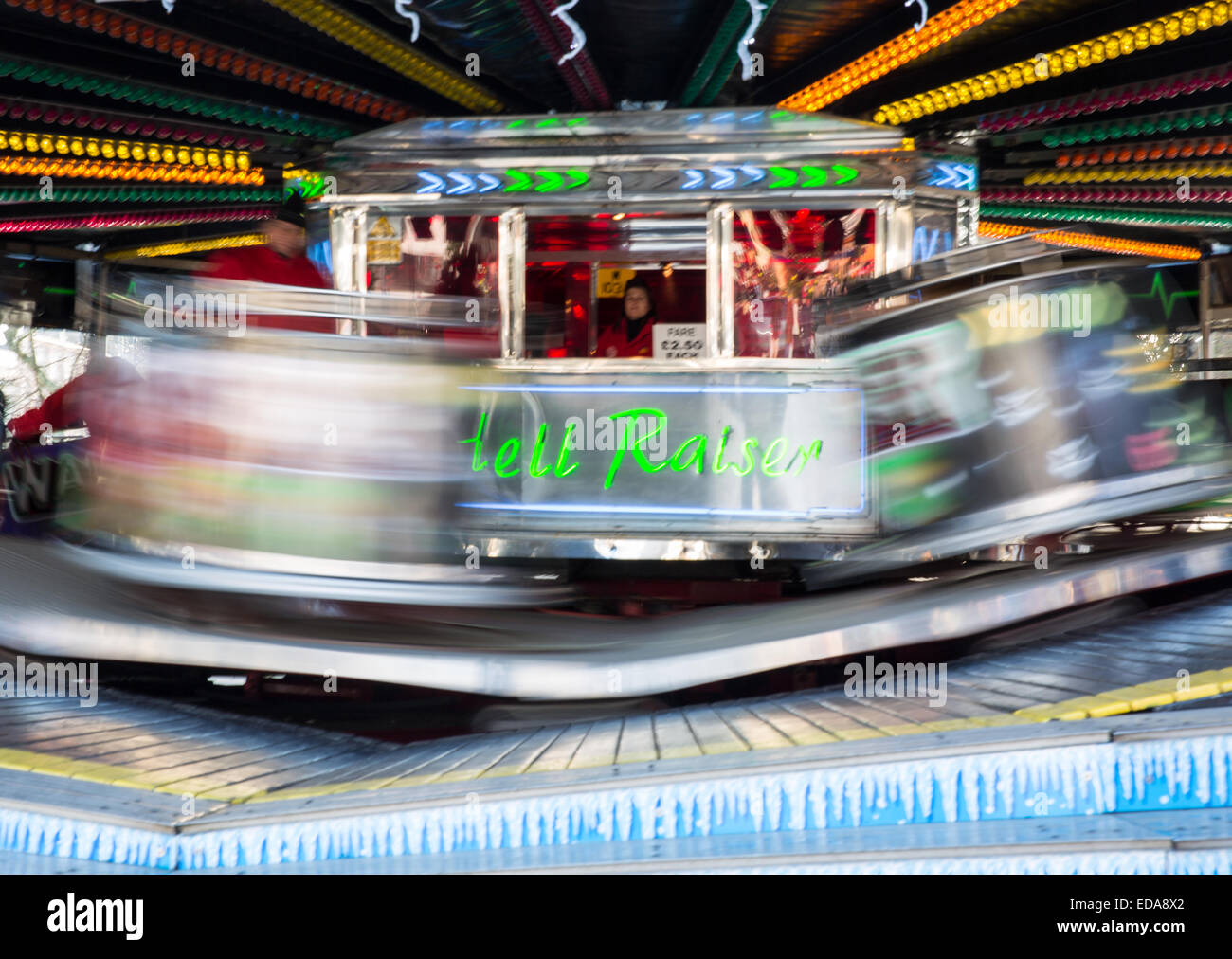 Whirling waltzers spin around at a fair ground ride. - Stock Image