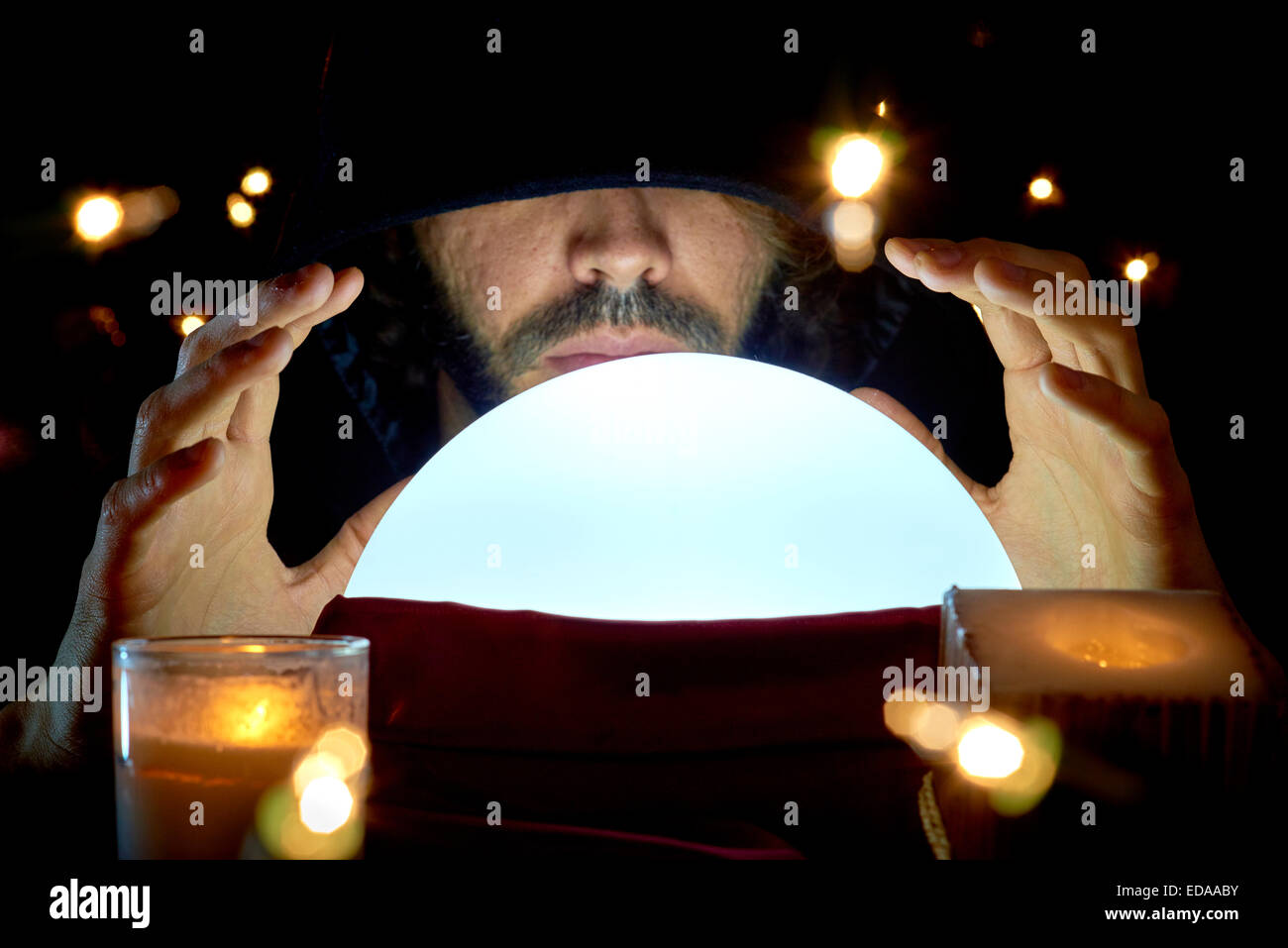 Very low key portrait of hooded man with eyes covered reading fortune on bright crystal ball, surrounded by candle - Stock Image