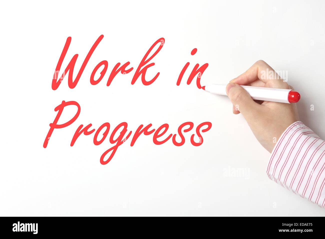 Business man writing work in progress word on whiteboard - Stock Image