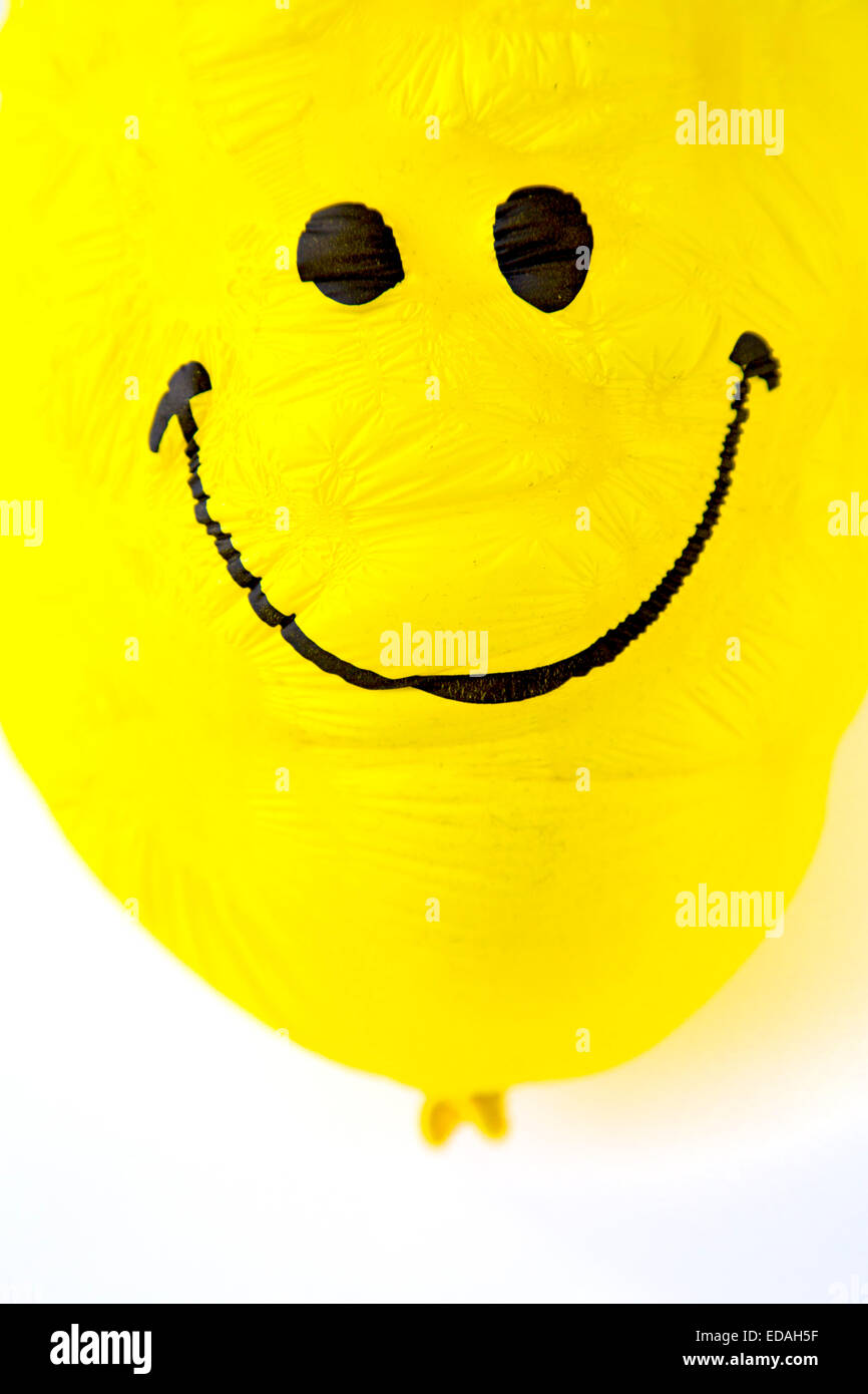 old Balloon, yellow, shriveled with friendly smiley face,  sunken, wrinkled Stock Photo
