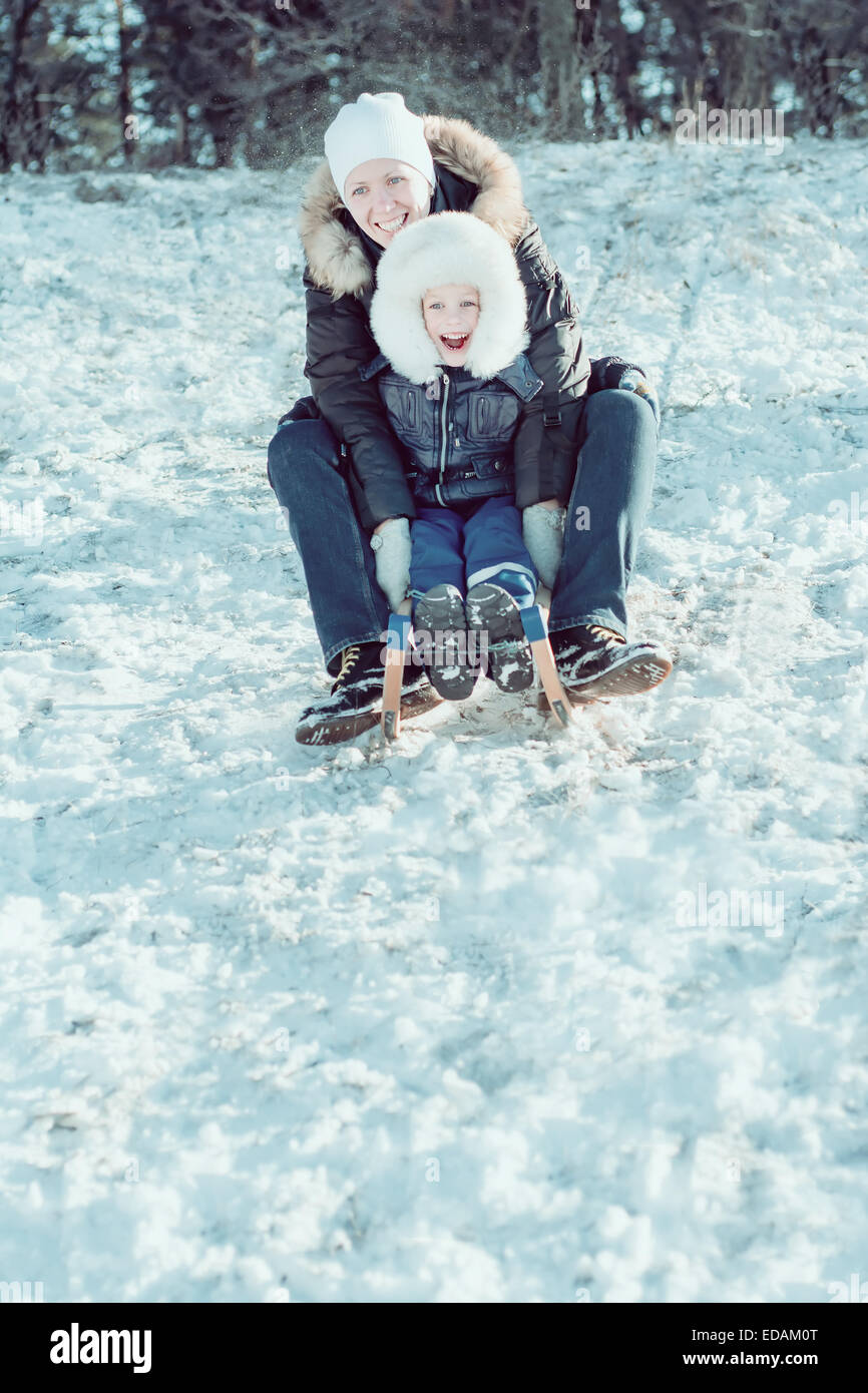 young beautiful mother and her little son on the sledge - Stock Image