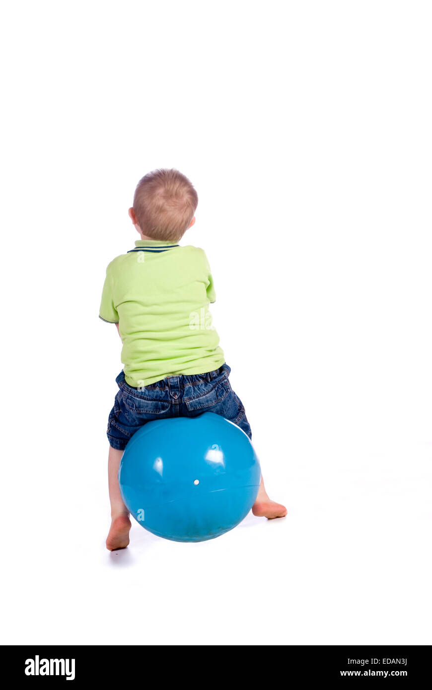 Boy playing in studio with space hopper toy - Stock Image