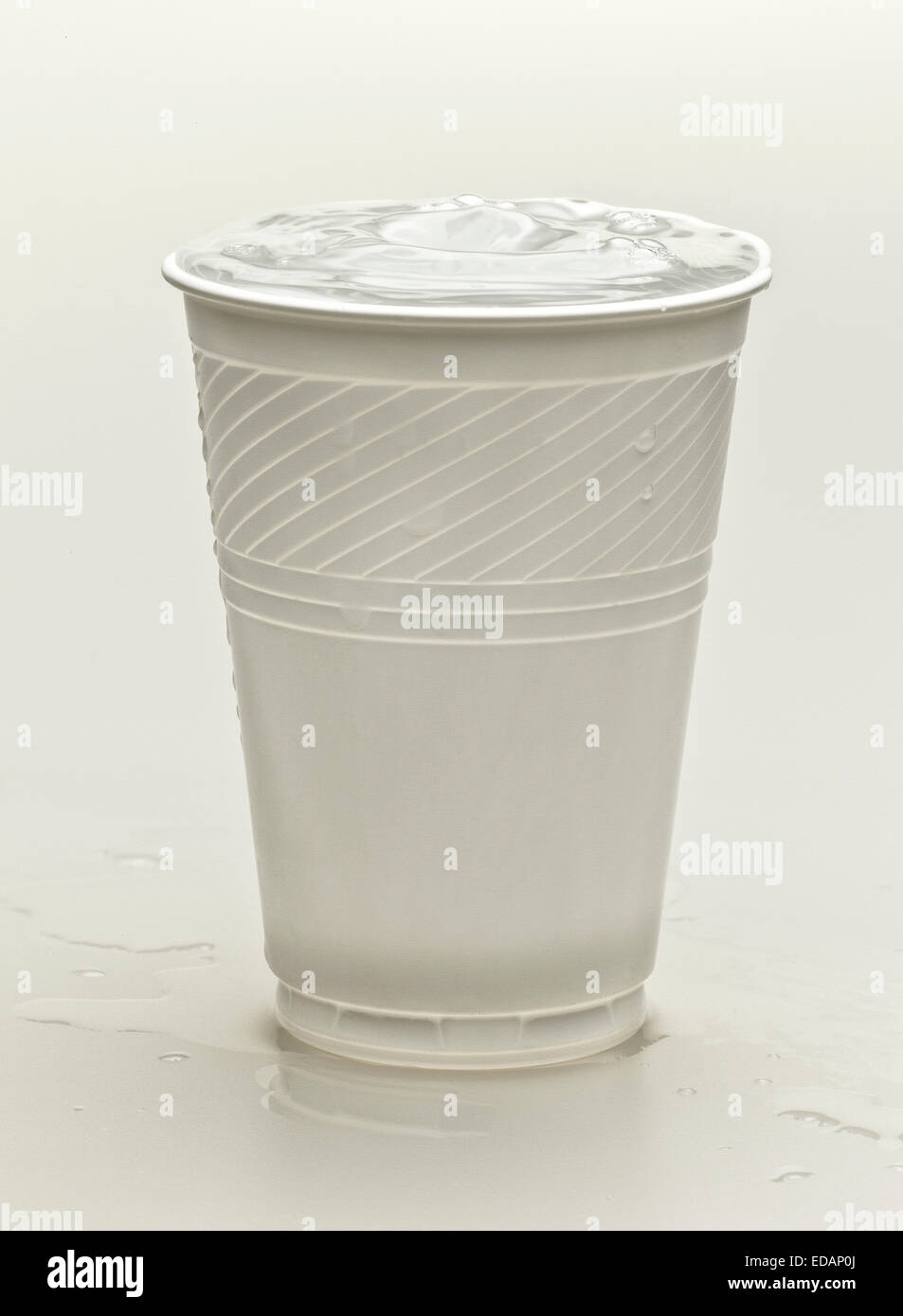 A white plastic cup of a white background containing water for a refreshing drink Stock Photo