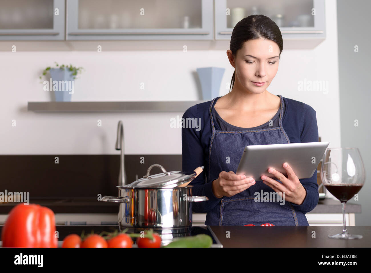 Young woman looking at a recipe on her tablet as she stands in the kitchen in front of a saucepan on the stove - Stock Image