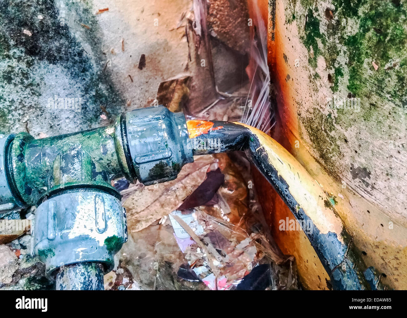 Leakage from old pipes in front of the house wall. - Stock Image