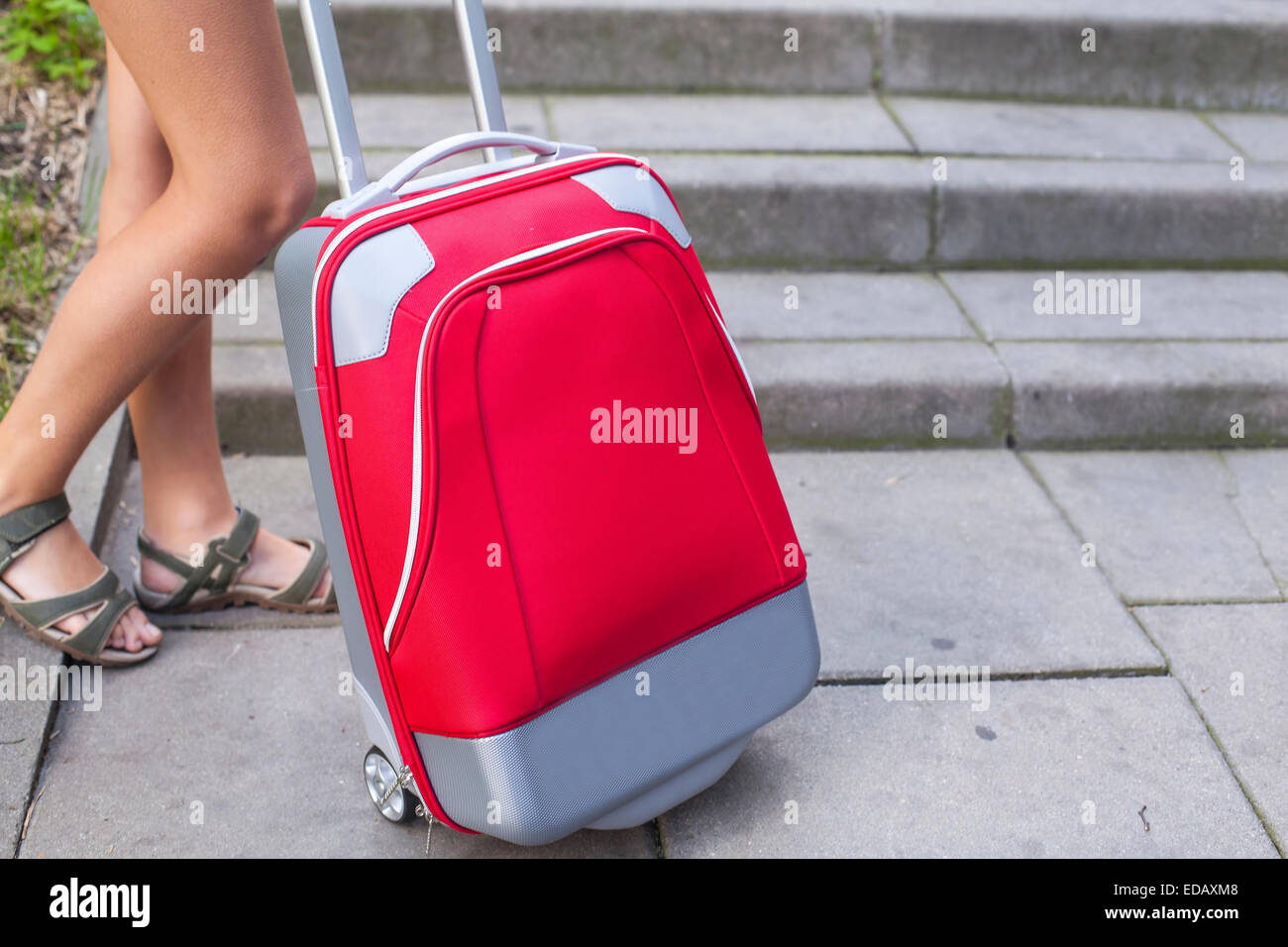 Closeup of the feet of a young girl near red travel suitcase. - Stock Image