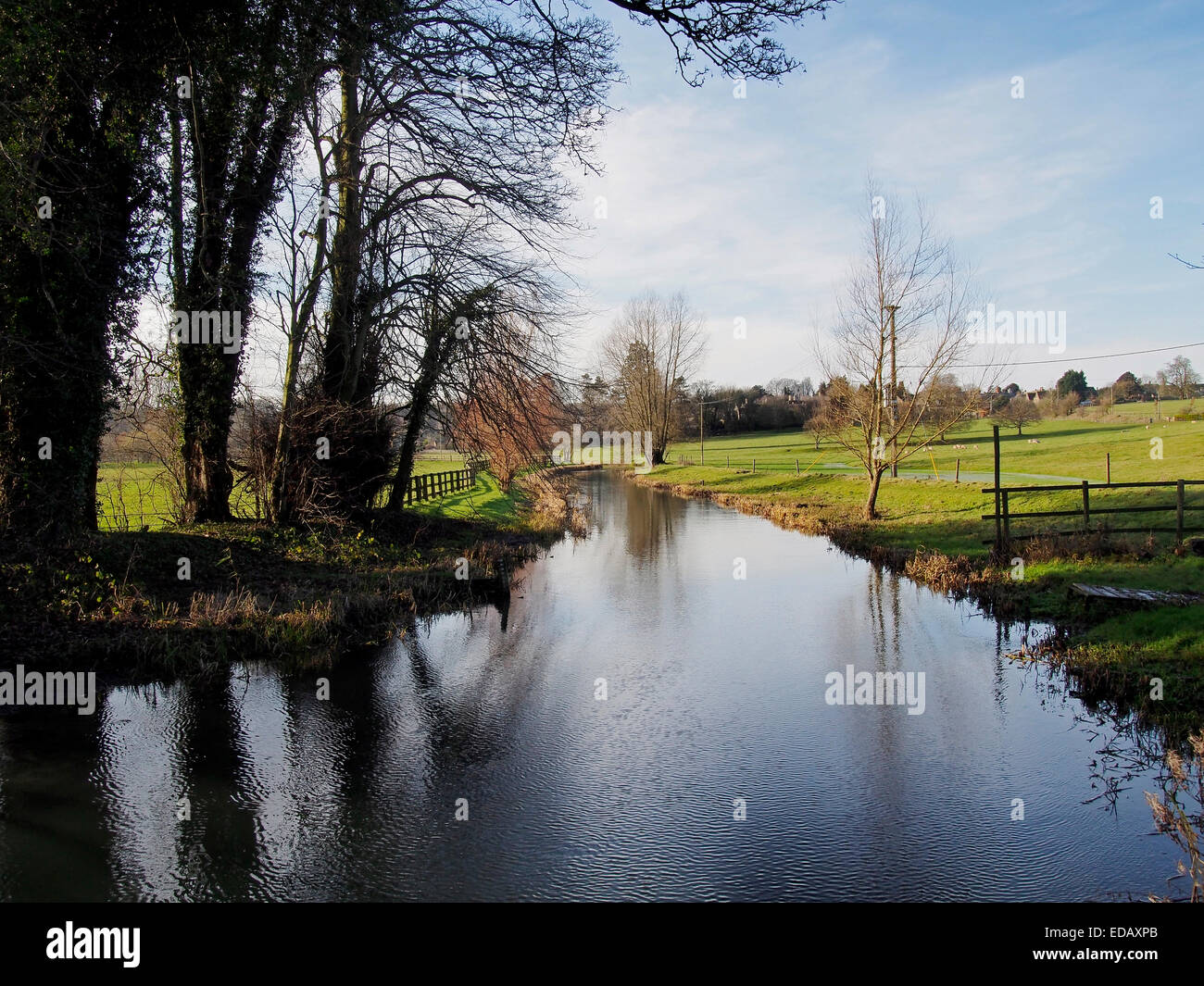 A bright & sunny winter scene on the River Colne looking west to Colne St Aldwyns from Hatherop, Gloucestershire, - Stock Image