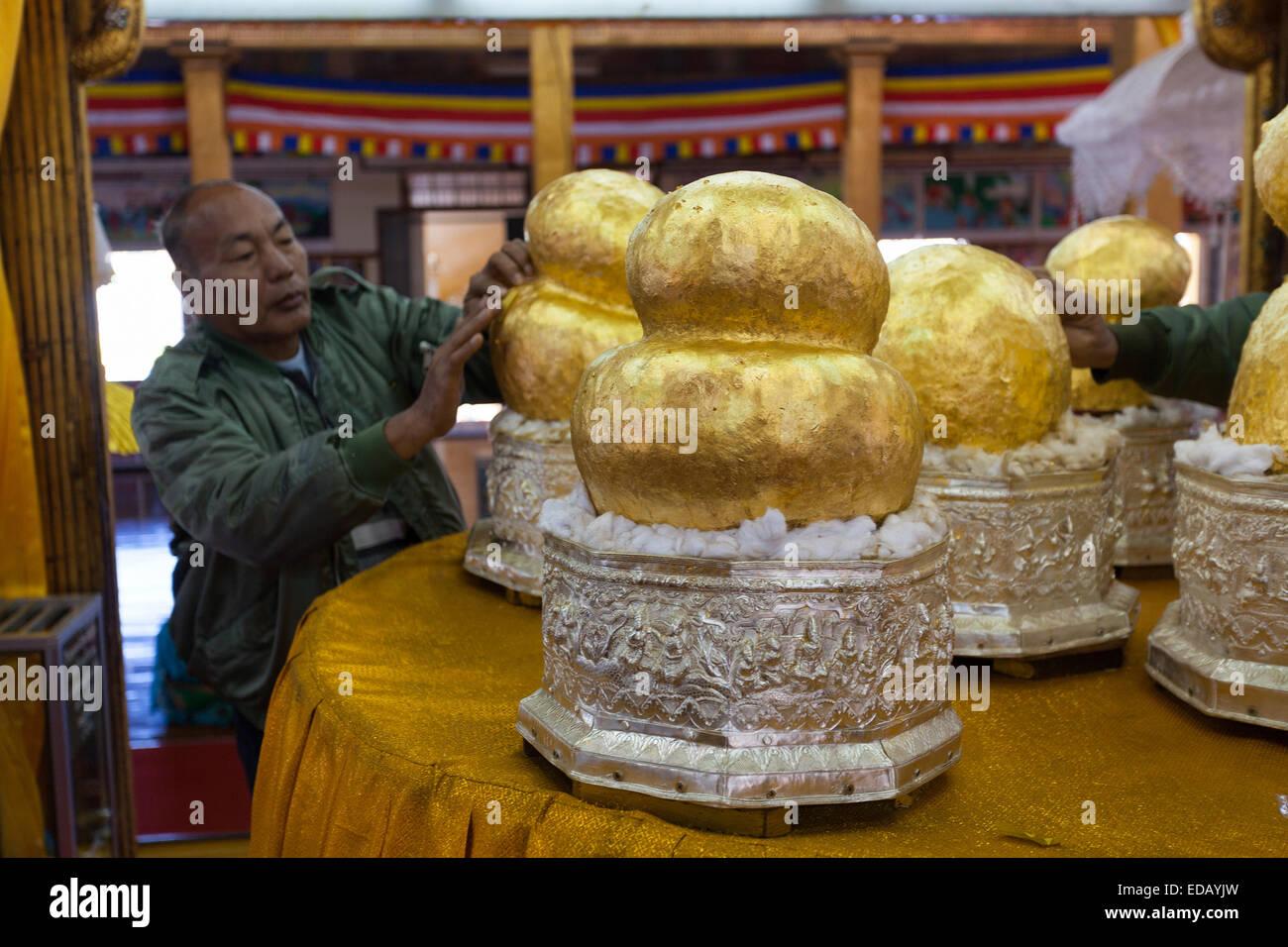 Worshiper putting gold leaf onto Buddha (now indistinguishable) Temple, Inle Lake, Myanmar - Stock Image