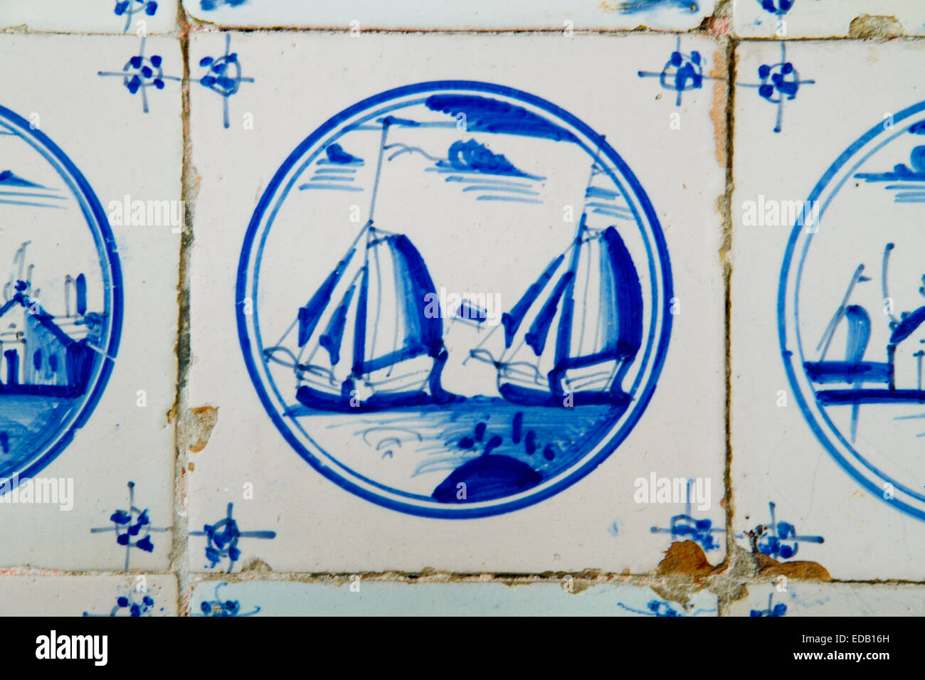 Painting of two sailing ships on an antique dutch tile on the kitchen wall of an old building - Stock Image