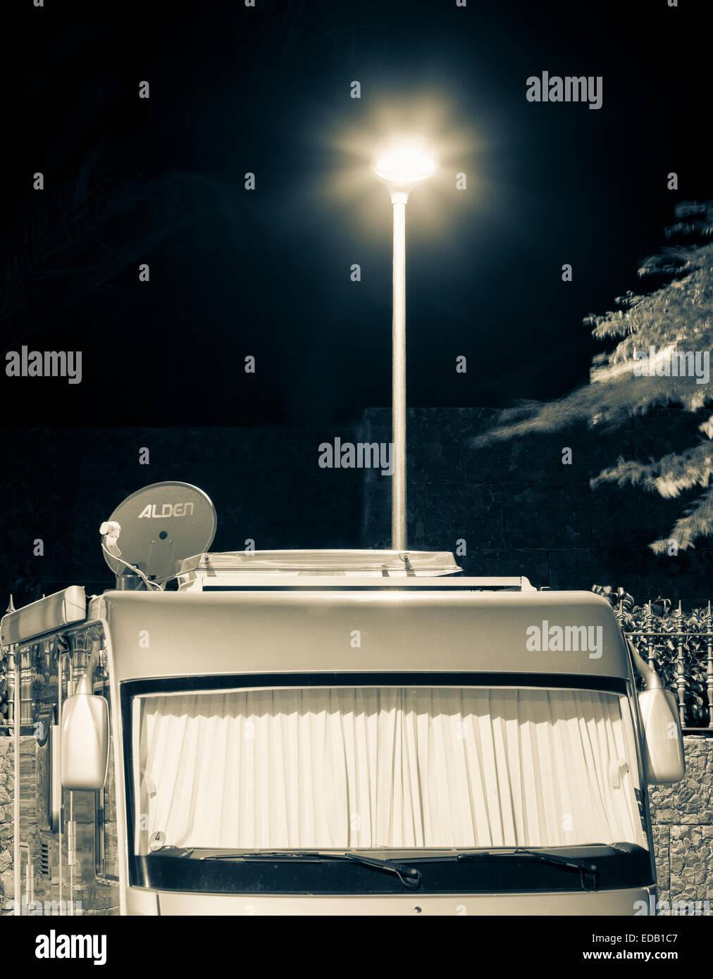 Campervan parked under street light in public car park in Spain - Stock Image